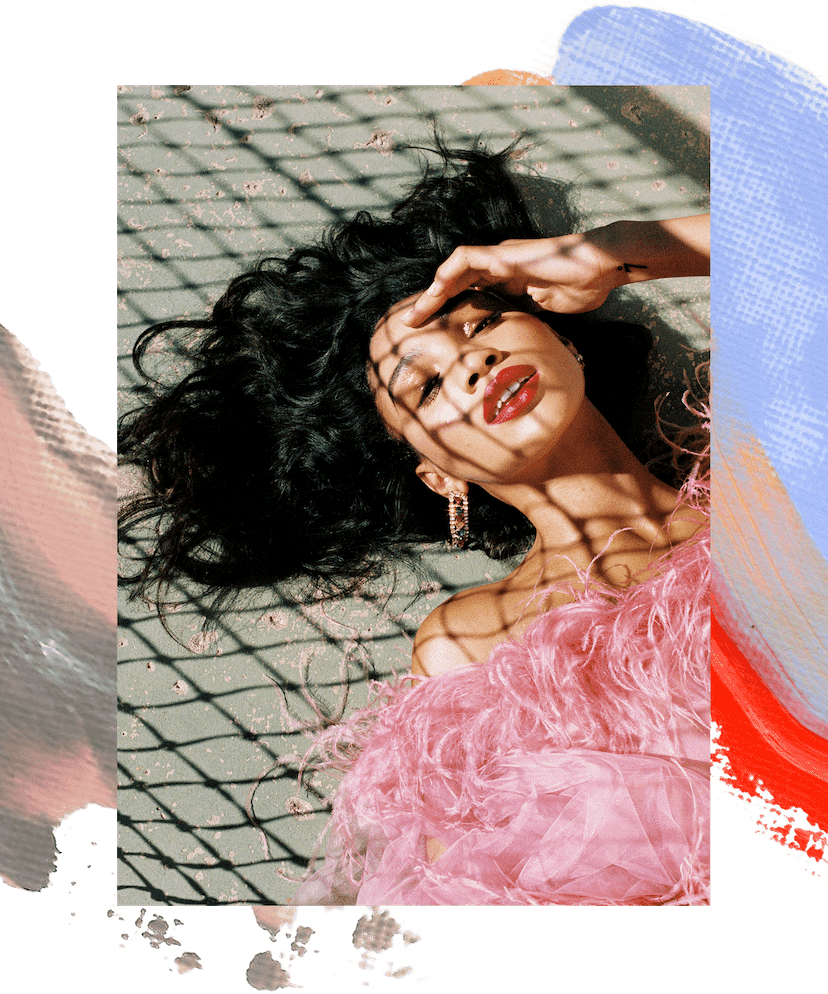 KNC Supa Beauty Balm in the back jean pocket of a model. She is also wearing a delicate pearl belt. Next to that is a photo of Lyric Mariah lying down on a tennis court. Her hair is long and lush around her face and she is wearing a pink feather dress. There is a decorative pink and blue paint swatch under these images.