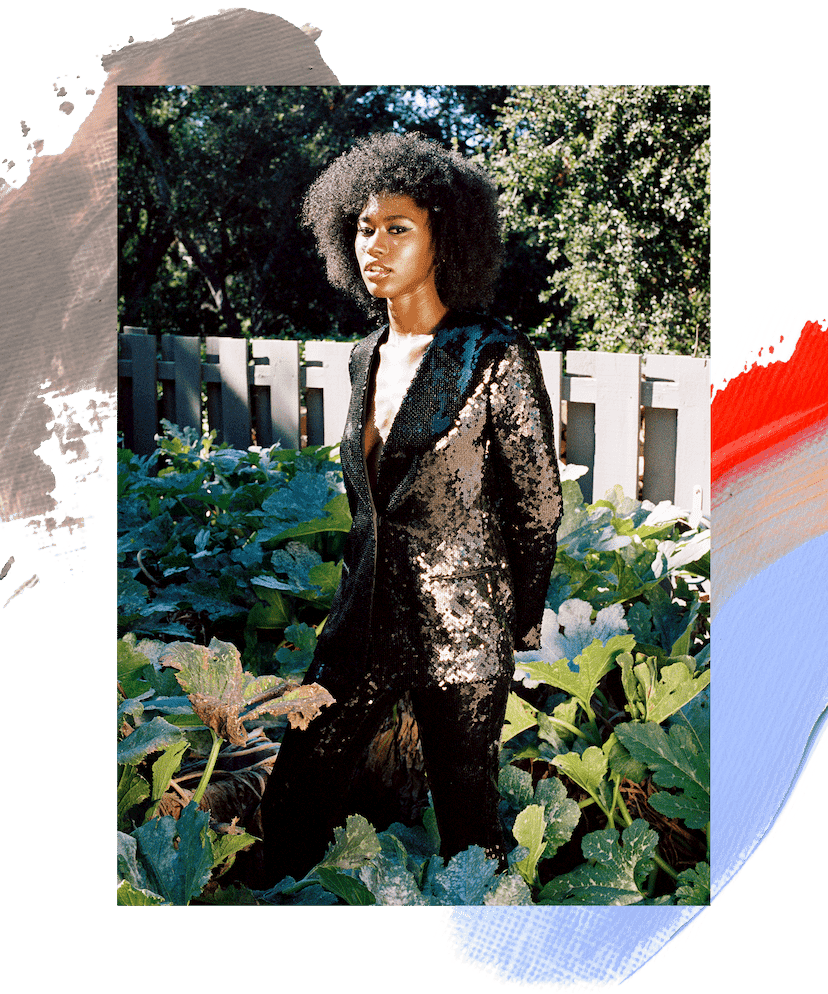 Amaya January model standing in a garden. She is wearing a black sequin blazer and has brown curly hair and a black cat eye makeup look. A brown, orange, red, and blue paint swatch is illustrated beneath the image.