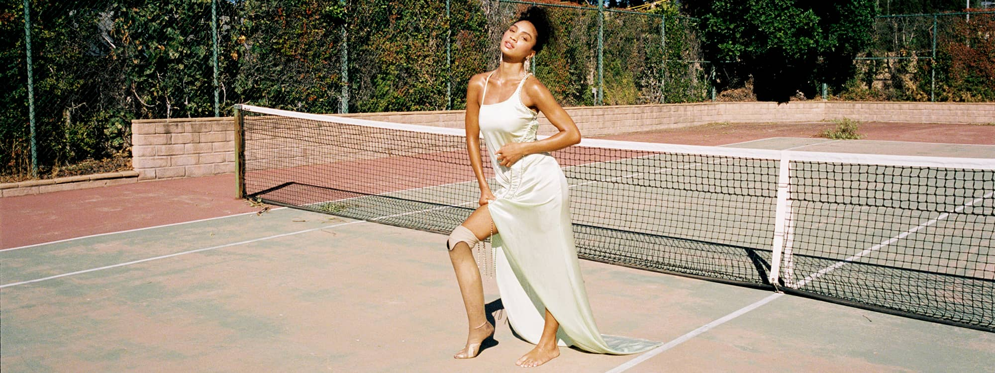 Model Lyric Mariah stands on a tennis court wearing a long silk green dress with her hand on her hip. Her hair is in an updo and her skin is gleaming in the sun. She is popping out her prosthetic leg.
