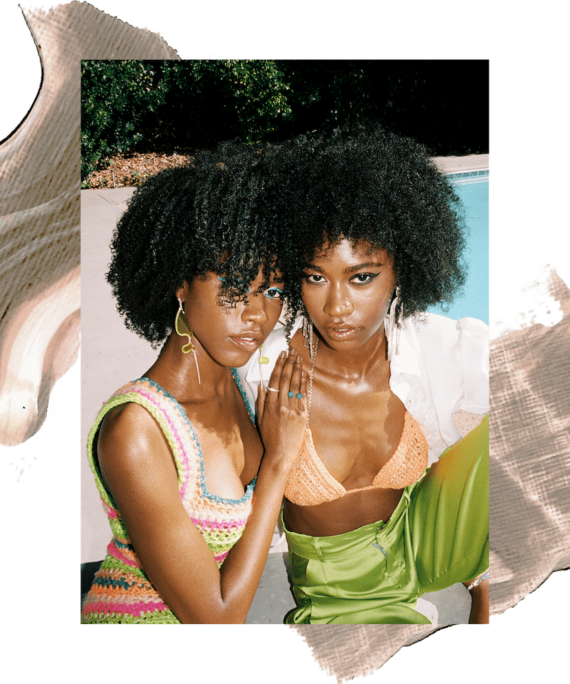 Model Amaya January stands outside in a peach crochet bikini top and silver earrings. She has brown curly hair and is standing in front of trees and a bright blue sky. In the second image she is seated next to her sister Alana January and wearing green silk pants and a white button-down shirt that is open to reveal the bikini top. Her sister is wearing a pink and green crochet dress. There is an illustration of brown and peach paint behind them.