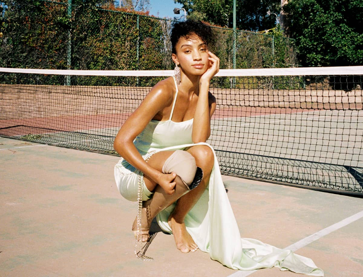Model Lyric Mariah wearing a long green silk dress and kneeling on a tennis court with her arm wrapped around her prosthetic leg. She has curly brown hair and her makeup is soft and glam.