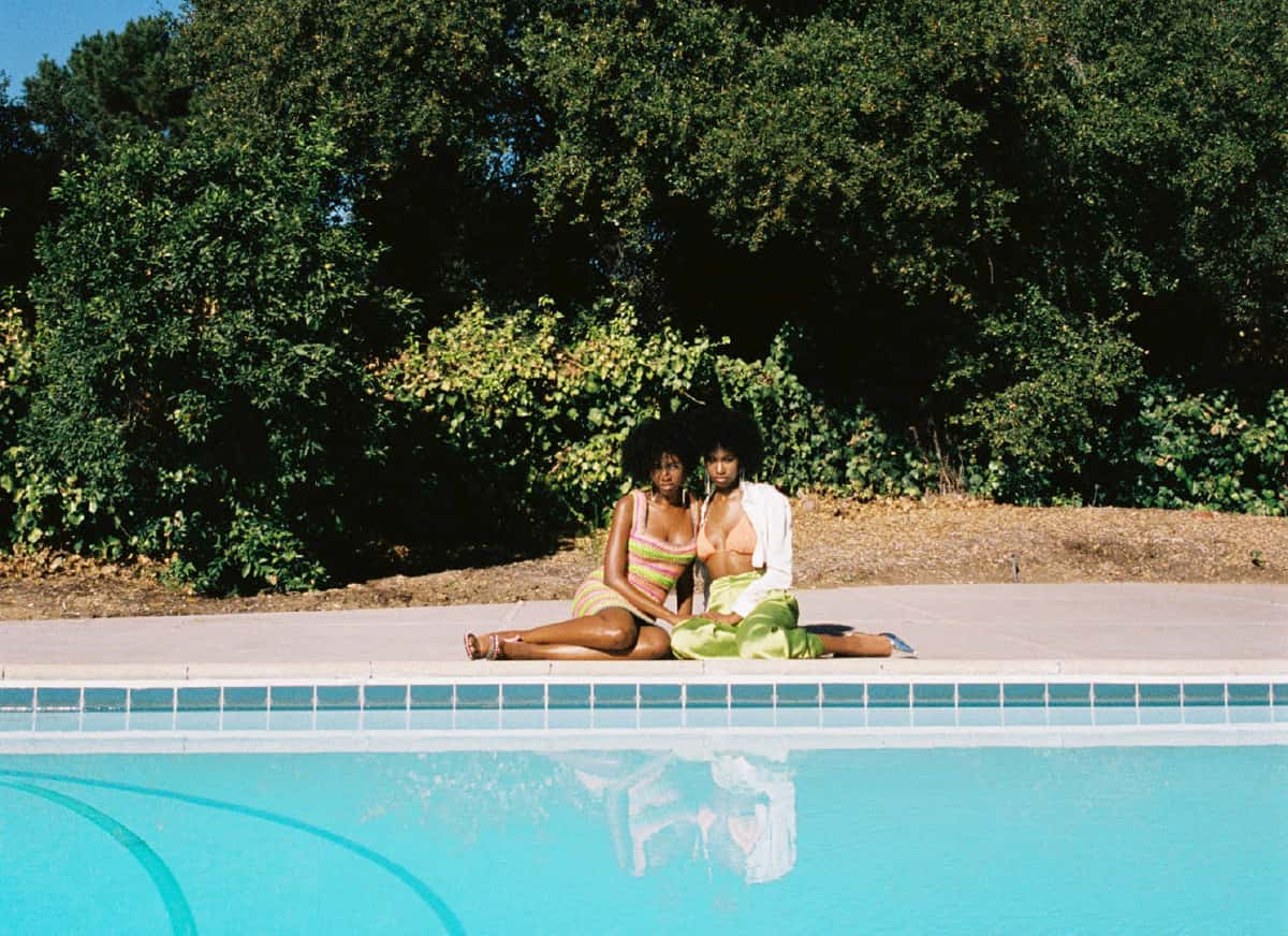 Twins Alana and Amaya January sit near the edge of the pool with a large tree behind them. One is wearing a green skirt, pink bikini top, and white button down. The other is wearing a crochet dress.