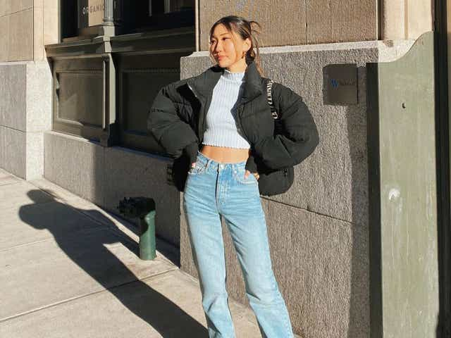 Woman standing on a street wearing a cool outfit and blue pair of jeans