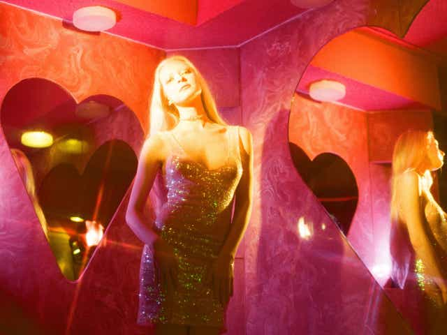 Woman in gold dress standing in pink room with heart shaped mirrors and star-shaped light