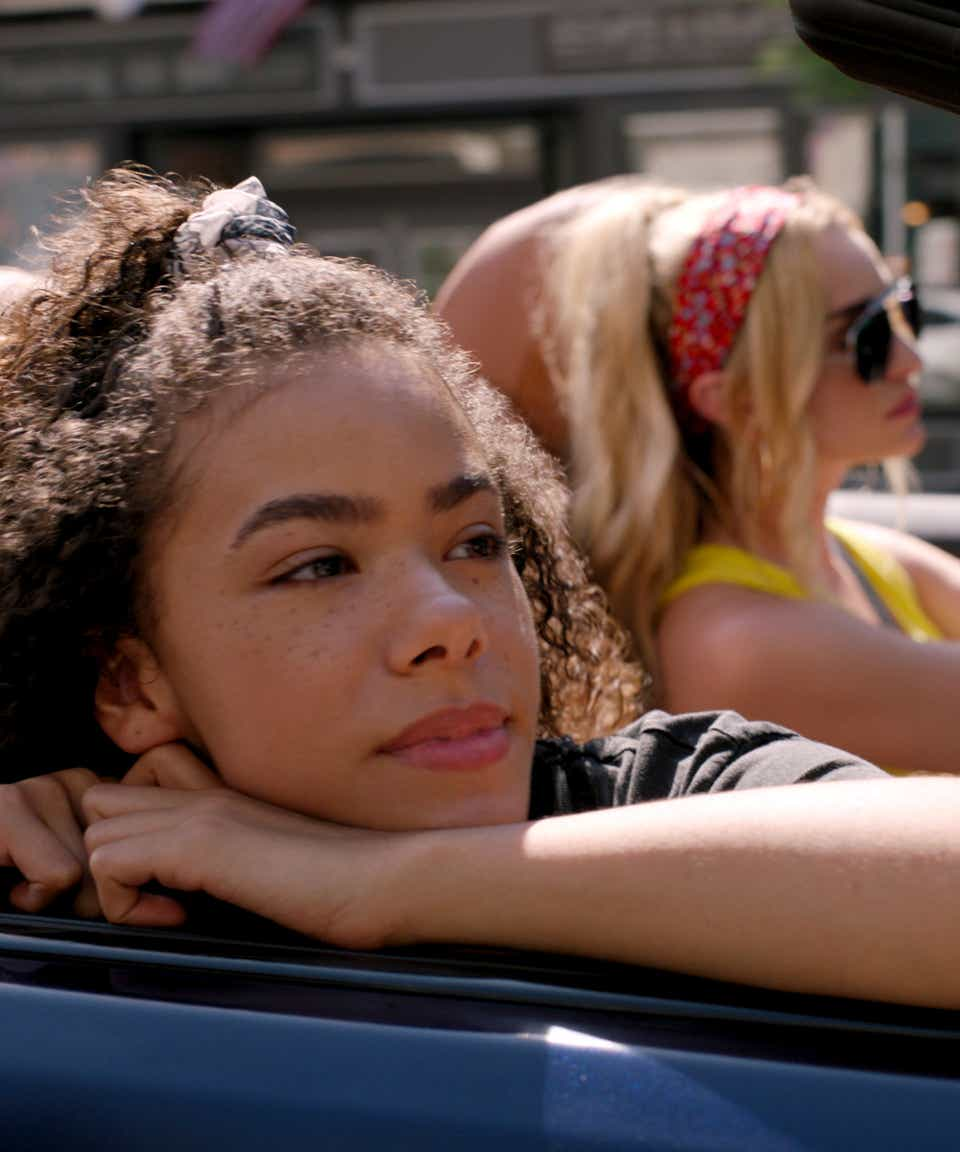 A mother is driving her teen daughter in a car in this still from the new movie Ginny & Georgia