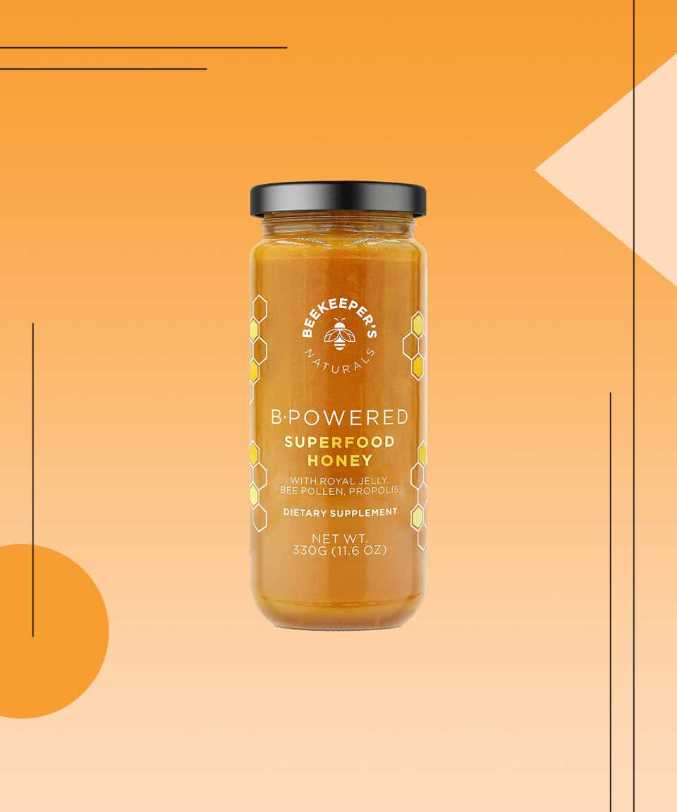 Jar of superfood honey over an orange and peach background with shape and line design elements.