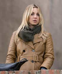 Kaley Cuoco appears in The Flight Attendant. She is wearing a tan leather trench coat with a brown scarf.