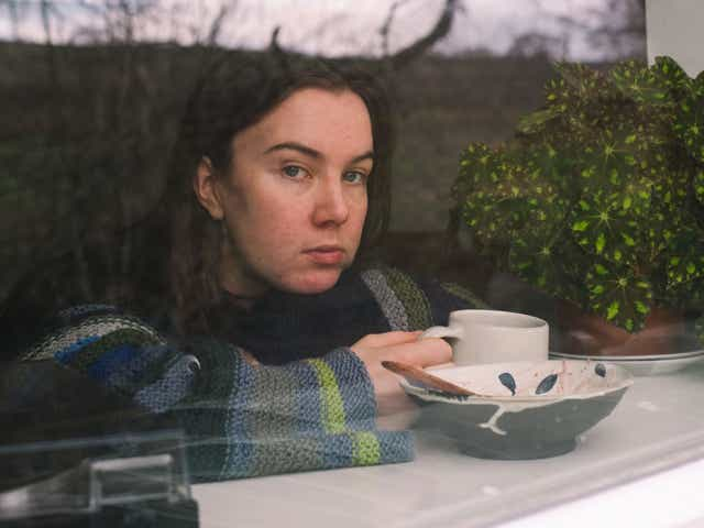 Model gazes out of a window whilst holding a mug, with reflections of the outside world on the window