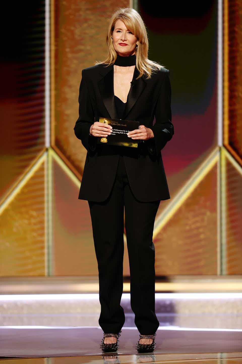 Laura Dern on stage at the Golden Globes in a Givenchy tuxedo with a bra top.