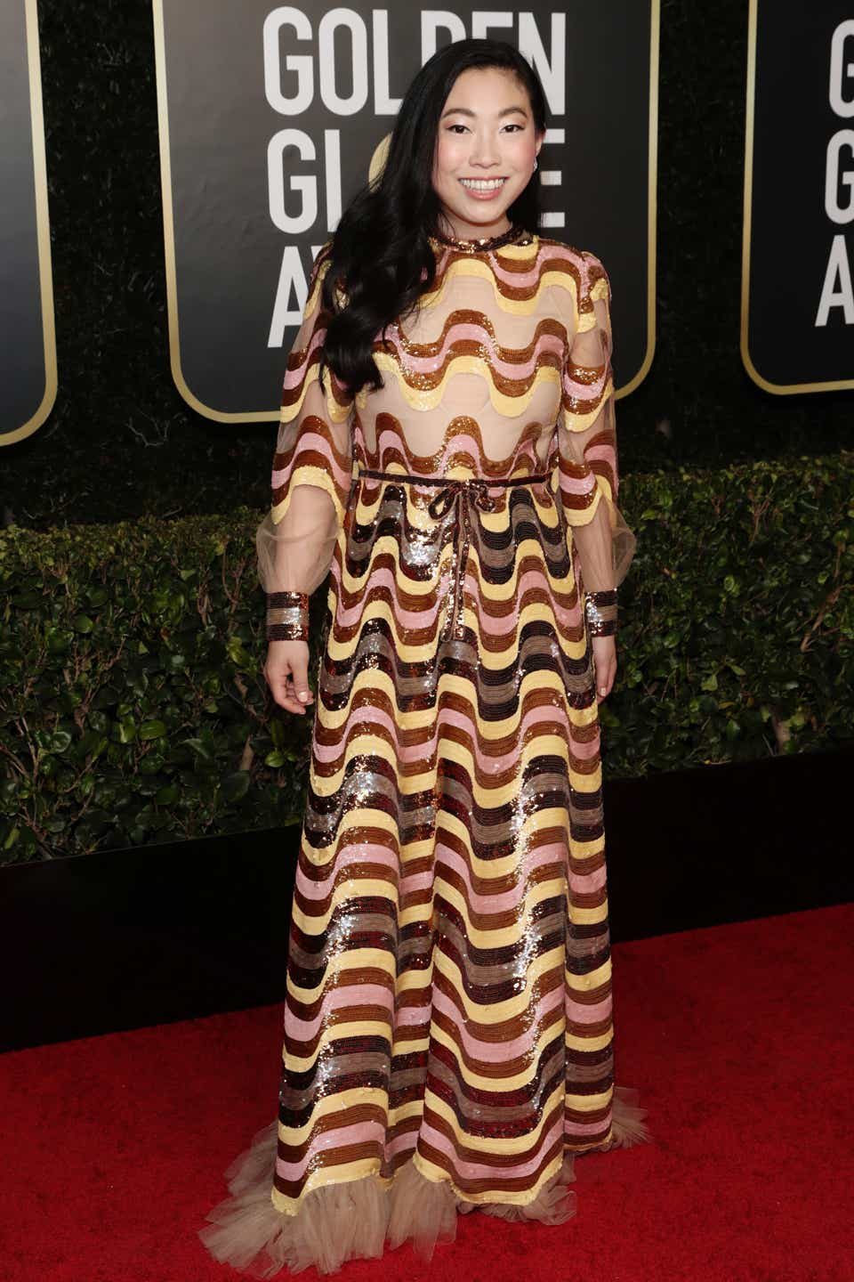 Awkwafina wearing a patterned dress on the Golden Globes red carpet.