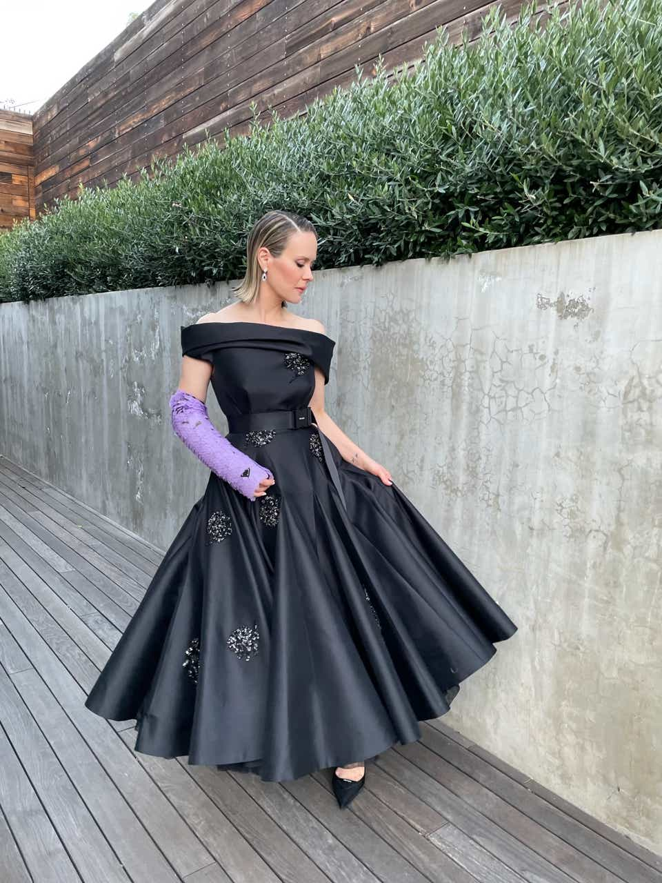 Sarah Paulson posing outside in a black Prada dress with a purple cast for the Golden Globes.