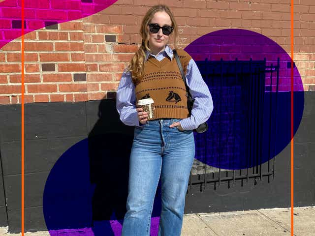 Maddie Sensible wearing a brown sweater vest over top a blue button down shirt with jeans and loafers.