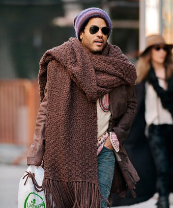 Lenny Kravitz seen wearing colorful beanie and oversized scarf with an embroidered sweater, torn jeans and fringed boots.