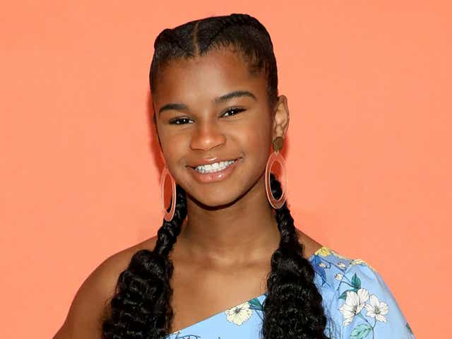 Marley Dias smiling wearing a blue floral dress with two cornrow braids.