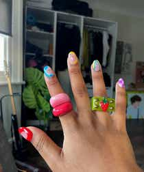 Image of someones hand modelling 2 colourful resin rings