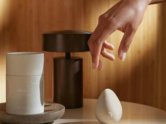 Hand reaching for Maude's new egg-shaped drop massager, resting on a nightstand against a wooden wall.
