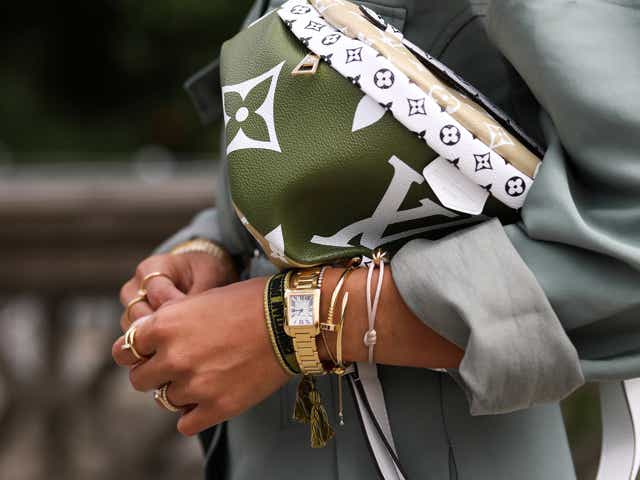 A street-style model wears a soft green boiler suit by The Frankie Shop, gold bracelets, and carries a green Louis Vuitton Bag.