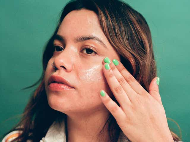 Model applying product to her cheek. the model has scarred/blemished medium-light skin and dark hair