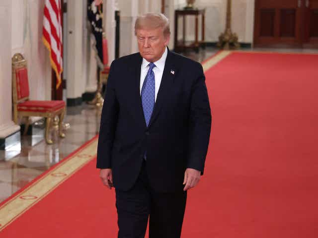 President Donald Trump walks to the East Room.
