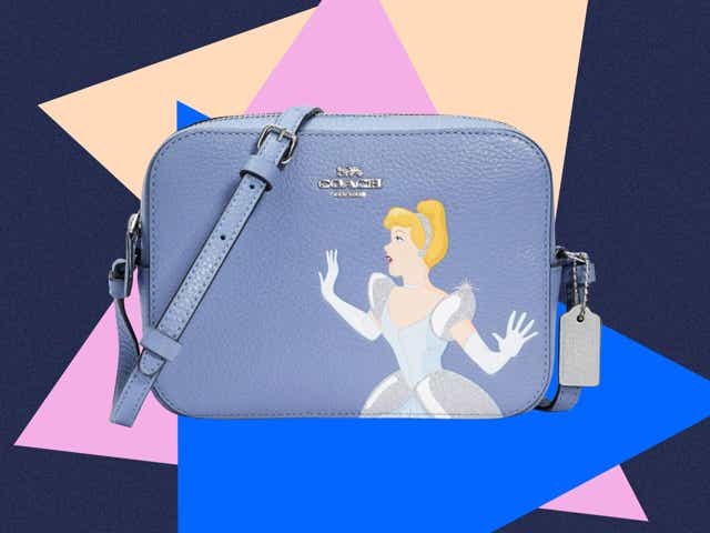A cross-body handbag printed with the image of Cinderella, from the Coach Outlet x Disney Princess collaboration.