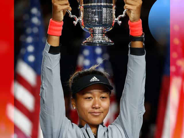 Naomi Osaka holding a trophy over her head.