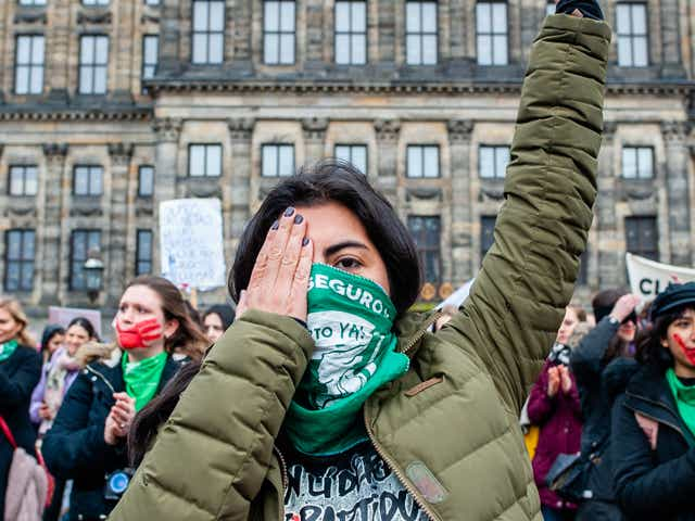 Women with red hands painted on their faces and green scarfs are performing performing 'The Rapist is You' during the Women's march