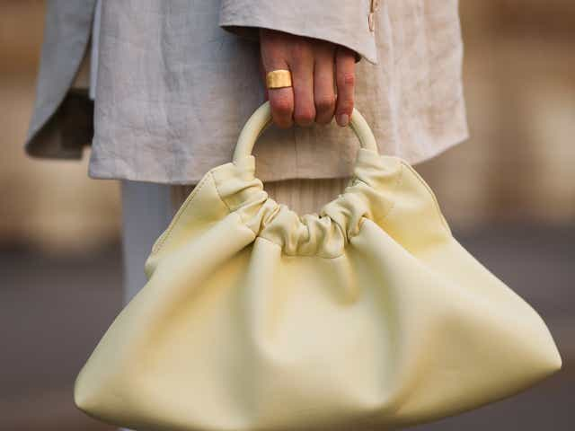 A street-style model wearing a taupe linen blazer and carrying a yellow Nanushka bag.