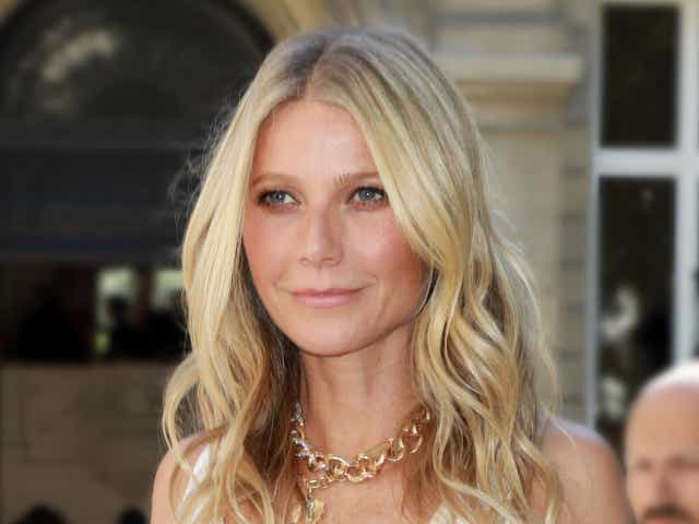 Gwyneth Paltrow poses in a white gown and a gold chain necklace.