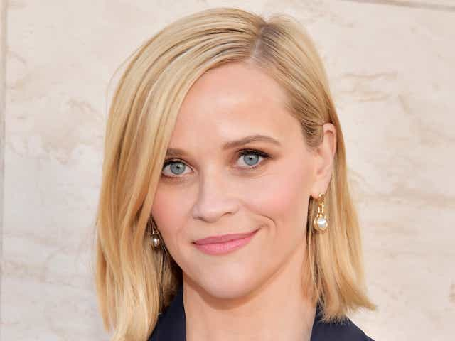 Reese Witherspoon wears a navy blazer and gold pearl earrings.