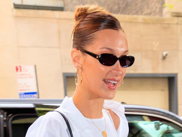 Bella Hadid wears a white shirt, gold necklace, and small-frame sunglasses.