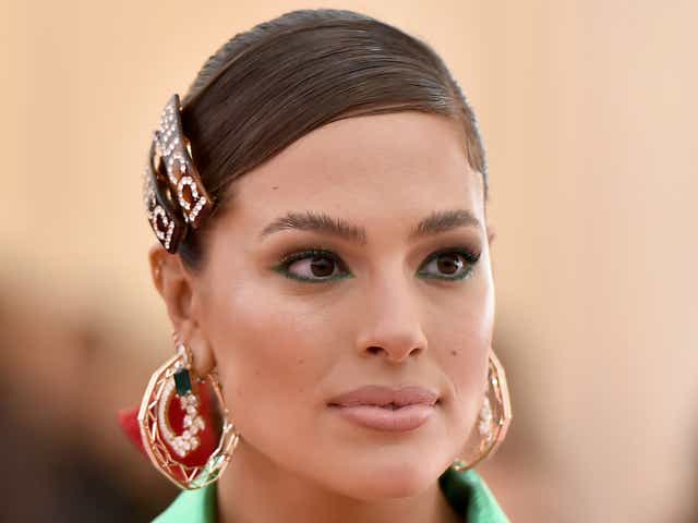 Ashley Graham wearing a Gucci hair clip, hoop earrings, and a Gucci robe dress.