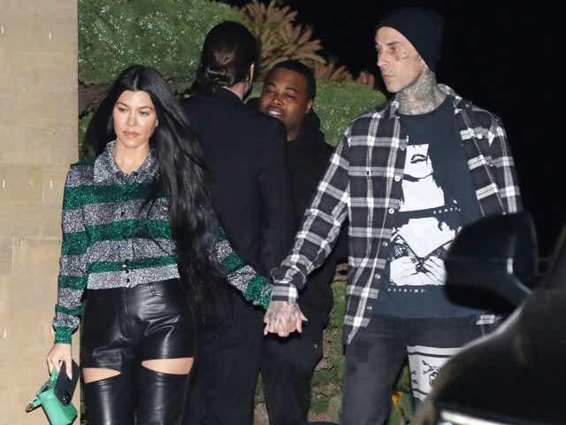 Kourtney Kardashian and Travis Barker holding hands.