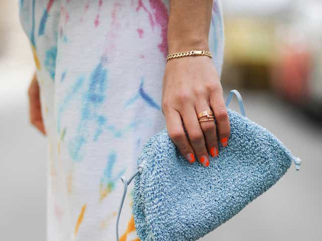 Street-style model wears tie-dye joggers, a white blouse, and carries a light blue clutch.