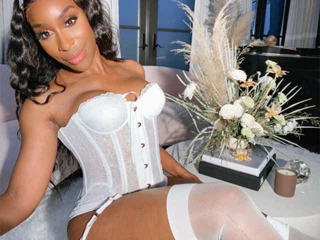 Jackie Aina modeling a Savage x Fenty corset.