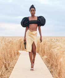 Jacquemus model wearing a black, puff-sleeved crop top with a yellow midi skirt at the spring '21 show.