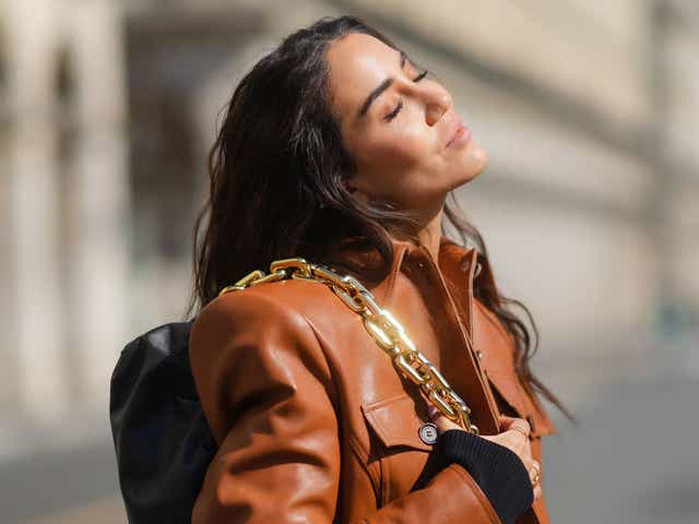 Tamara Kalinic wears a brown leather jacket from Magda Butrym, a black low-neck top from Khaite, a black leather pouch bag with golden chain from Bottega Veneta, and large flared blue denim jeans pants from Valentino.