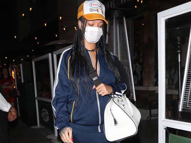 Rihanna wearing a trucker hat, tracksuit, and flip-flop heels.