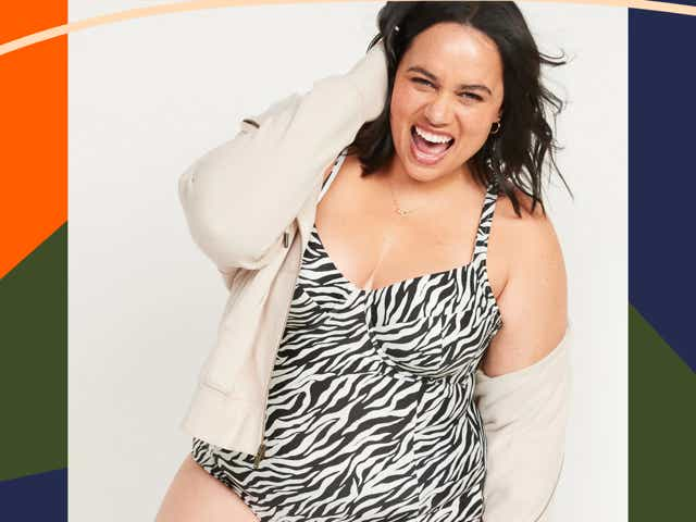Model wears a zebra one-piece with a cream colored jacket while smiling very big.