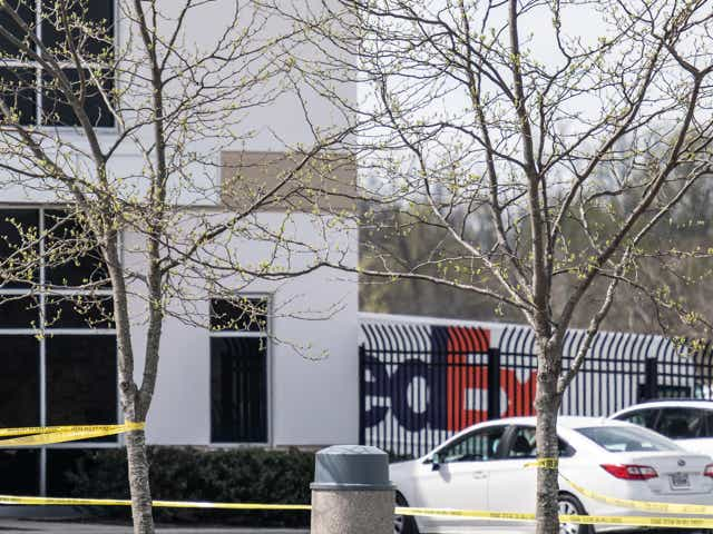 Caution tape and parked vehicles are seen in the parking lot of a FedEx SmartPost on April 16, 2021 in Indianapolis, Indiana. The area is the scene of a mass shooting at FedEx Ground Facility that left at least eight people dead and five wounded on the evening of April 15.