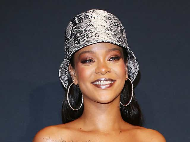 Rihanna wearing a snakeskin bucket hat and matching dress on the red carpet.