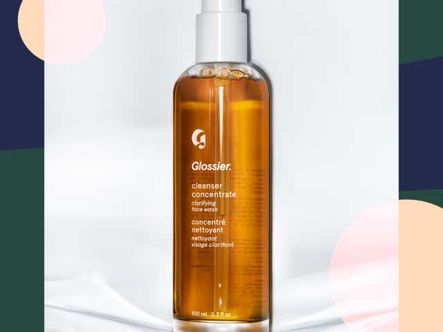 Bottle of Glossier's Cleanser Concentrate against a background of pink, green, and beige bubbles