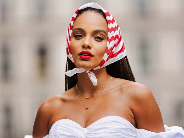 Alicia Aylies wears a red and white striped scarf over the head, a white pleated / gathered off-shoulder low-neck top with ruffle and puff sleeves, a golden necklace