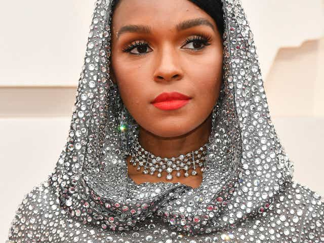Janelle Monae wearing a sequined hooded gown and a red lip.