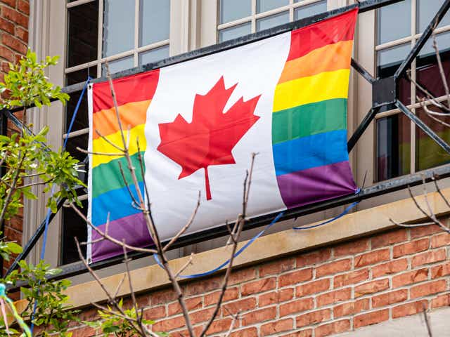 Canadian flag with pride colors hangs on a balcony.