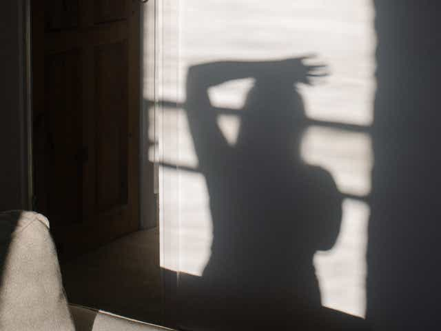 Image of a person's shadow on a wall, they have their arm resting on the top of their head