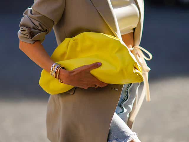 Leonie Hanne wears a golden necklace, a white cropped top, a gray oversized long blazer jacket, a yellow leather puff bag, and ripped pale blue denim shorts.