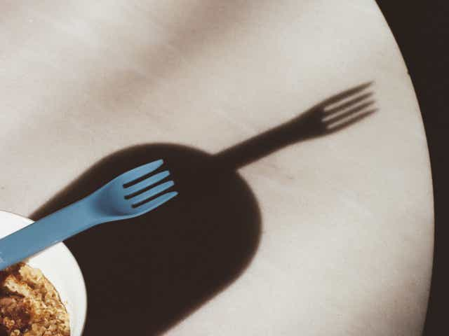 Fork leaning on a bowl, casting a shadow against a table
