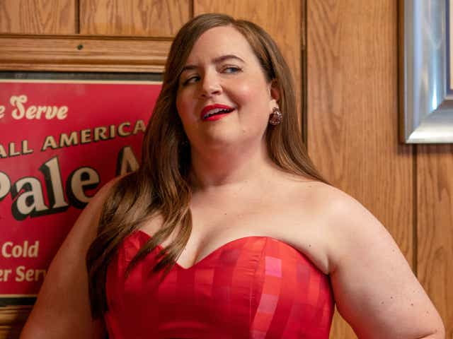 Aidy Bryant poses in a strapless red dress as Annie in an episode of Shrill.