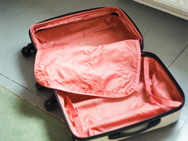 An image of an empty, open suitcase with red lining.