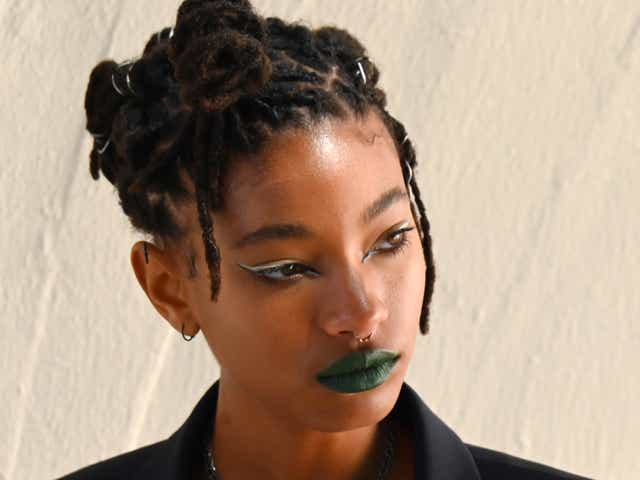 Willow Smith wearing green lipstick and a black vest.